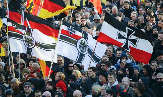 Supporters of anti-immigration right-wing movement PEGIDA (Patriotic Europeans Against the Islamisation of the West) carry various versions of the Imperial War Flag (Reichskriegsflagge) during a demonstration march, in reaction to mass assaults on women on New Year's Eve, in Cologne, Germany January 9, 2016. REUTERS/Wolfgang Rattay