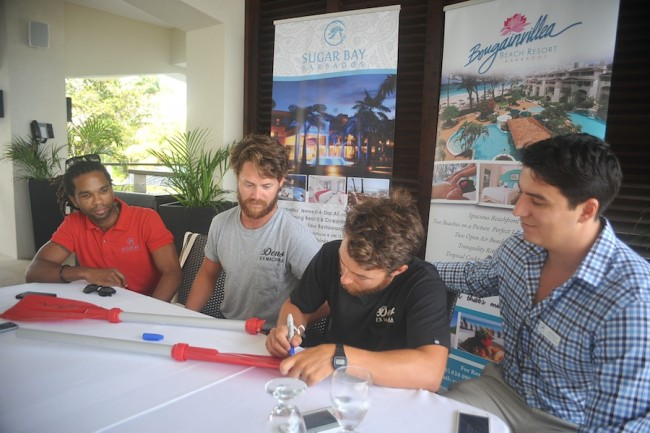 Jamal Griffith, marketing manager of Sugar Bay Barbados (at left) and director Morgan Seale (at right) looking on as Tempest Two rowers Tommy Caulfield and James Whittle sign oars.