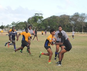 Emperors scrum half Mikyle Walcott (with ball) fending off a determined challenge from Tridents' Anquan Lynch.