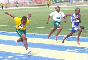 Shatori Eversley (left) of St Bernard's Primary dips at the line to win his heat of the under-13 boys 100m.