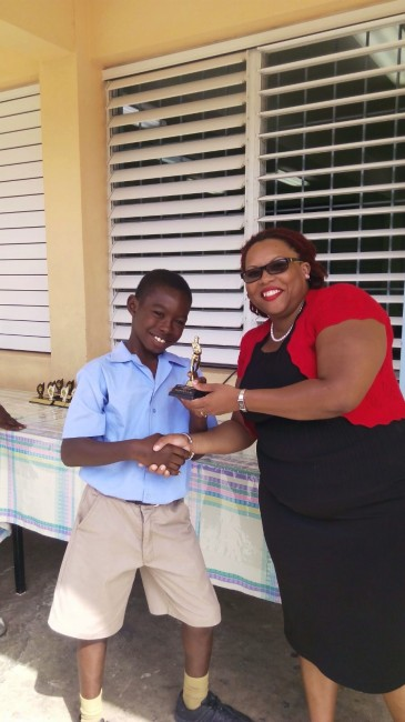Victor ludorum Jakeem Pollard, under-9 boys division champion from Red House receives his prize.