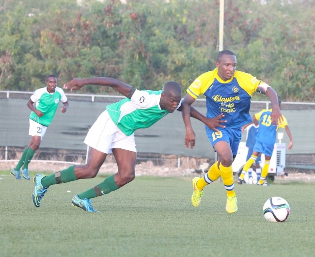 (From left) Barbados Defence Force Sports Programme goal scorer Tyrell Gibbons takes on Clayton's Kola Tonic Notre Dame's captain Renaldo Gilkes.