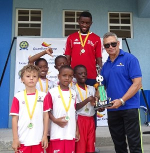 Amado Marcano, branch manager at Guardian Life of the Caribbean, presents the champions trophy to captain Matthew Clarke of Kick Start.