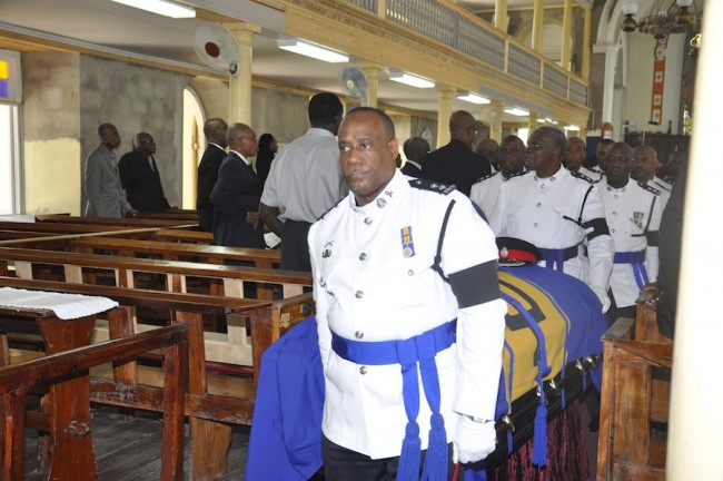 Former Senior Superintendent Clyde Evanson Clarke's casket being taken out of the church by police officers.