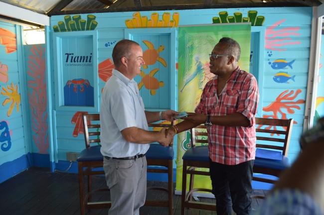Smokey Burke presenting a CD to Tiami Catamaran Cruises divisional manager Joshua Roach.