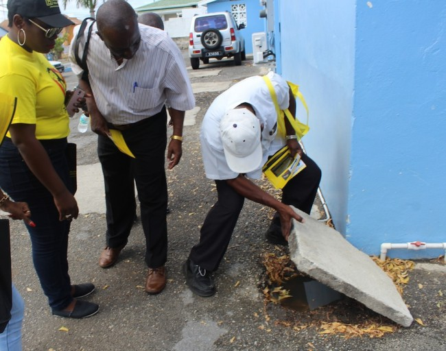 From left, Marketing Executive of Barbados Yellow Pages Sabrina Greenidge looks on as environmental health officers Basil Pilgrim and Stanley Alleyne carry out a mosquito breeding  inspection.