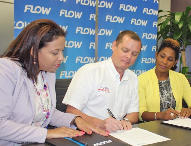 President of Vaucluse Raceway Greg Cozier (centre) signs a sponsorship agreement with telecoms provider Flow as head of marketing Shelly Ann Hee Chung (left) and director of communications Marilyn Sealy look on.