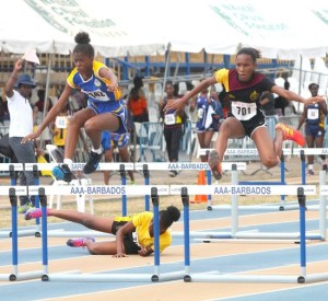 T'shanni Payne of Scotiabank Springer Memorial goes over the junior girls 75m hurdles and ahead of Harrison College's Tia Hinds.