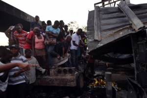 Haitians look at the damage after an explosion at a gas station in Hinche today.