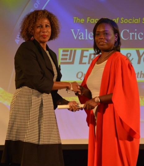 Ernst & Young's Jasmine Babb presenting that organization's scholarship award to Valencia Crichlow.