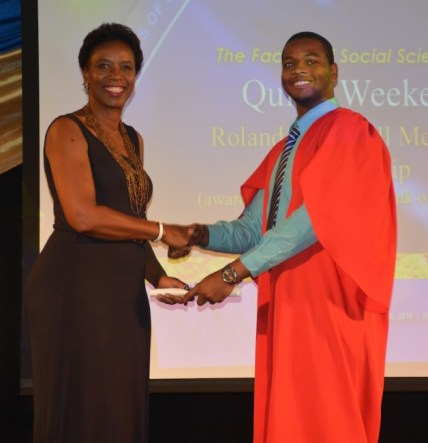 Barbados Central Bank's Laurie Blackman (left) presenting the Roland Craigwell Memorial Scholarship to Quinn Weekes.