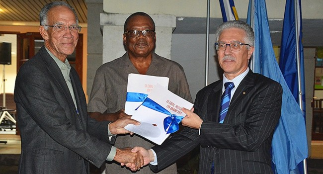 CDC Chairman Dr Trevor Hassell (left) and Minister of Health John Boyce pose with copies of the Global Report on Diabetes they received from PAHO representative Dr Godfrey Xuereb (right).