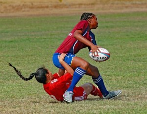 Barbadian Jayde Adams (with ball) being tackled by Trinidadian Kimberly Ting Shen.
