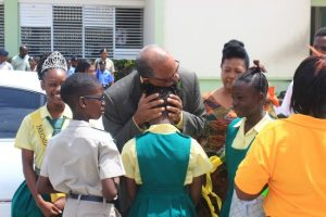 Outgoing Principal Jeff Broomes (centre) greets some of his students as his wife Margaret looks on.
