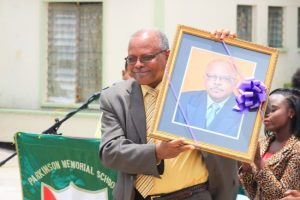 Outgoing principal Jeff Broomes holding up the  portrait of himself which he presented to Parkinson Memorial.