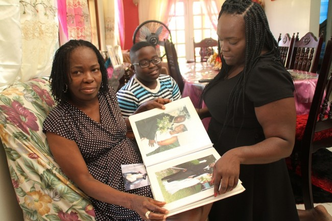 From left, Livingston Eversley's widow Joycelyn flipping through their wedding album, along with their grandson Donte and their daughter Latoya.