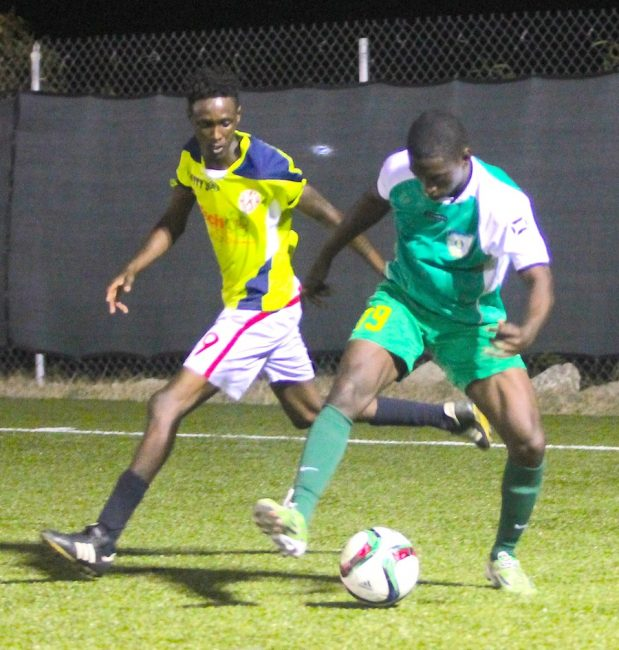 Raheim Sargeant of Barbados Defence Force Sports Programme looks to play the ball past Rinaldo Phillips of Ellerton. (Morissa Lindsay)