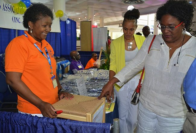 Opposition Leader Mia Mottley checks out the 'rush' covered stool. At left is Blind and Deaf Association member Cheryl Griffith and at centre is Opposition MP Santia Bradshaw.