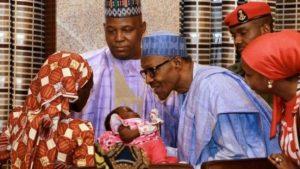 Amina Ali Nkeki (facing away from camera) showed her child to President Buhari.