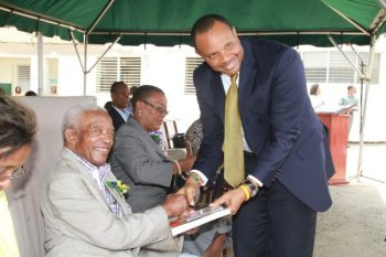 Irving Burgie presenting a copy of his biography to Minister of Finance Chris Sinckler.