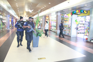 Policemen attached to the Guard and Emergency Branch walk through Gulf City Mall, La Romaine, Wednesday after security forces were put on high alert in the wake of audio threat claiming ISIS may target malls across the country over the weekend.