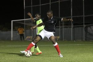 Rommel Bynoe of Brittons Hill is strongly tackled from behind by Pinelands' midfielder and goal-scorer Rasheed Greaves. (Pictures by Morissa Lindsay)
