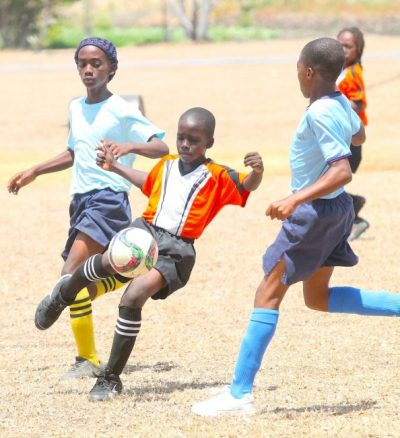 Shamar Clarke (center) scored two goals for Bayley's Primary and here dribbled past Terryke Gittens (left) and Rashawn Waithe of St Mark's Primary. (Pictures by Morissa Lindsay)