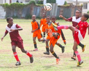 Tashon Weekes of Westbury Primary (second left wearing orange) and Joshua Roett of St Mary's Primary clash for the ball.