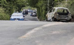 The burned car belonging to slain 22-year-old student Sara Di Pietrantonio is seen along a street in the outskirts of Rome on Monday.