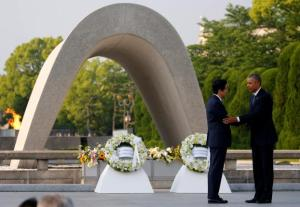 America's President Barack Obama (right) puts his arm around Japanese Prime Minister Shinzo Abe after they laid wreaths in front of a cenotaph  at Hiroshima Peace Memorial Park in Hiroshima, Japan.