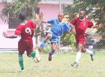 Bay Primary goal scorer Shakeem Kellman takes on Hilda Skeene Primary's defence of Sean Brathwaite and Joziah Burgess.