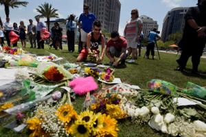 Chris Drozd, left, and Stefan Salvatore leave flowers and pictures for victims of Sunday's nightclub shooting at the Dr Phillips Performing Arts Centre in Orlando, Florida, Monday.