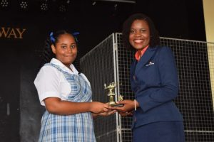 Alisha Ali, for reading over 50 books, receiving her trophy from Nicole Hinds  of Guardian General Insurance Ltd.