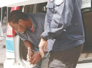 Glen Dalrymple is taken out of a police vehicle outside the Arima Magistrates' Court Tuesday.