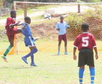Hilda Skeene Primary defender Sean Brathwaite clears the ball away from Kemar Butler of Bay Primary.