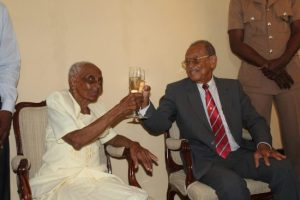 Scting Governor General Sir Philip Greaves toasts the island's latest centenarian Inez Miller.