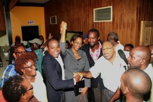 NUPW President Akanni McDowall holds aloft the hand of his legal representative Tanya Goddard as supporters throng him following tonight's unsuccessful no confidence motion against him.