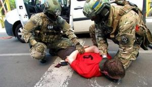 In this image, provided by the Ukrainian Intelligence Agency SBU on Monday, SBU agents detain a suspect at the Yahodyn border crossing  on the Ukrainian-Polish border, Ukraine.
