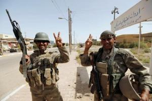 Iraqi soldiers gesture in center of Falluja, Iraq, on Friday.