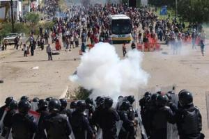 Riot police battle with protesting teachers who were blocking a federal highway in the state of Oaxaca, near the town of Nochixtlan, Mexico, Sunday.
