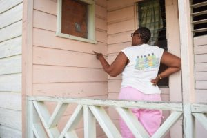 Here, Harriett Stuart points to one of the bullet holes left in her home.