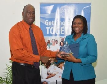 Sophia Thomas accepting her Unsung Heroes: Beyond the Call of Duty Award from CEO Dr. Dexter James.