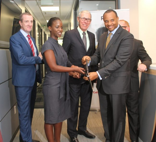 Here, Minister of Finance Chris Sinckler (right)is joined by businessman Ralph Bizzy Williams (second from right) and Managing Director of the Regus Business Centre Mark Linehan (left) in cutting the ribbon at today's opening.