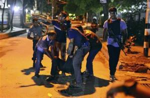 People help an unidentified injured person after a group of gunmen attacked a restaurant popular with foreigners in a diplomatic zone of the Bangladeshi capital Dhaka, Bangladesh, Friday.