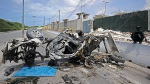 Somali soldiers stand on guard next to the wreckage of a car bomb outside the UN's office in Mogadishu on Tuesday.