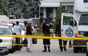 People watch from their front doors as police stand at a crime scene where three pople have died in an incident involving a crossbow, according to local media reports in the Scarborough suburb of Toronto, on Thursday.