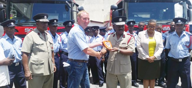 Dave Stone (left) from Angloco Limited handing over a thank you plaque to Chief Fire Officer Errol Maynard.