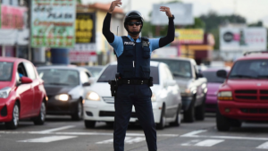 A transit police officer directs the flow of traffic at an intersection in San Juan, Thursday, after a massive blackout hit Puerto Rico Wednesday afternoon, leaving at least 1.5 million people without power overnight and into the following day.