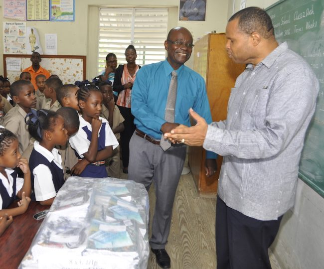 Minister of Finance Chris Sinckler and principal of Eagle Hall Primary School Orlando Jones shake hands following the donation of books to the school today.