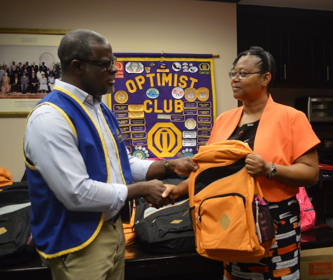 Member of the Optimist Club of Bridgetown Adrian Elcock (left) presenting Belmont Principal Pamela Ifill with one of the book bags.